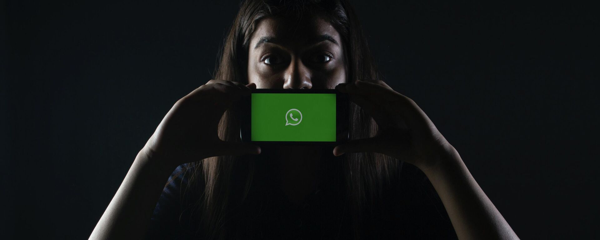 Una persona sostiene un móvil con el logotipo de WhatsApp - Sputnik Mundo, 1920, 05.08.2021