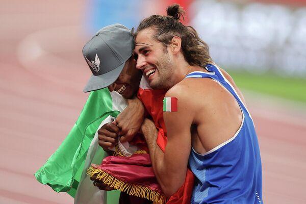 """Gianmarco Tamberi, de Italia, y Mutaz Essa Barshim, de Catar, entraron a la historia de los Olímpicos al decidir que compartirían la medalla de oro. Tamberi y Barshim empataron en la final del salto de altura. Al ser preguntados por el juez si querían seguir saltando para desempatar, el catarí le preguntó: """"¿Si no el oro es para los dos?"""". Ante la respuesta afirmativa del arbitraje, ambos se abrazaron y celebraron el título compartido. Este es el primer oro olímpico compartido en el atletismo desde 1912. - Sputnik Mundo"""