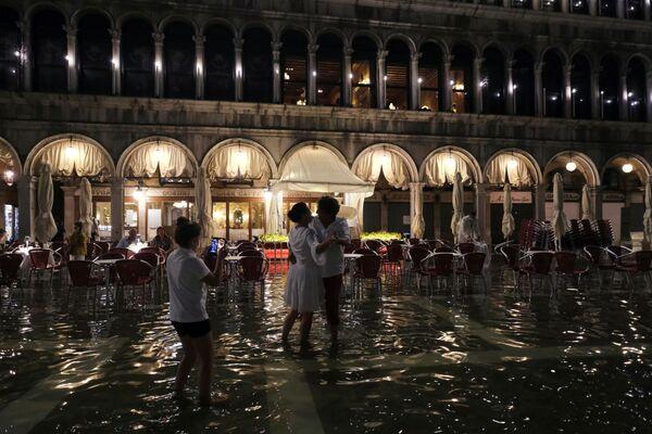 Una pareja baila en la plaza inundada. - Sputnik Mundo