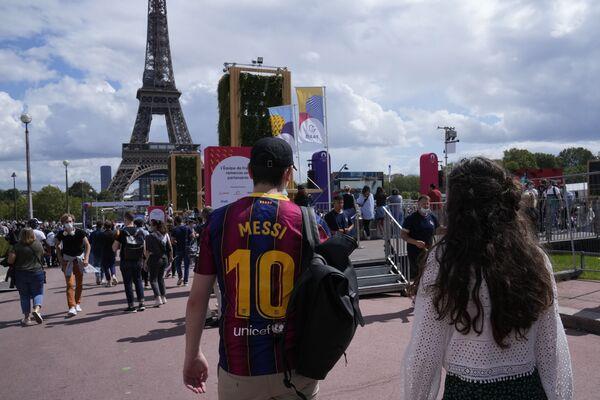Un visitante viste una camiseta de fútbol del FC Barcelona con el 10 de Lionel Messi mientras camina frente a la Torre Eiffel, en París - Sputnik Mundo