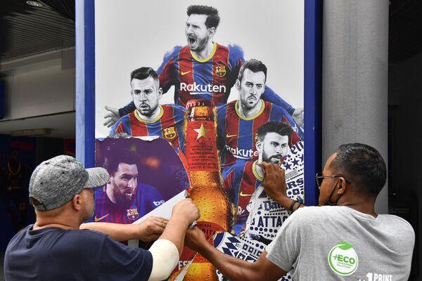 Los trabajadores del estadio Camp Nou de Barcelona retiran carteles que muestran al alero argentino Lionel Messi, quien firmó con el PSG - Sputnik Mundo