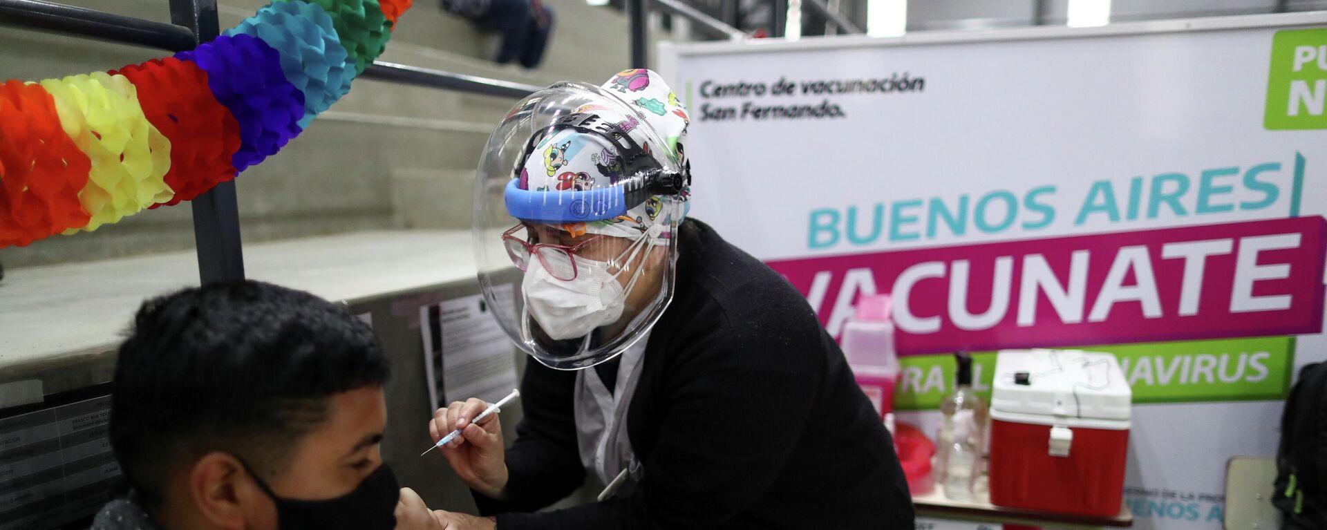 La trabajadora de salud Carla Díaz vacuna a Joel Villalba, de 17 años, con una dosis de la vacuna Moderna contra el coronavirus (COVID-19) en un centro de vacunación, en Buenos Aires, Argentina, el 9 de agosto de 2021 - Sputnik Mundo, 1920, 11.08.2021