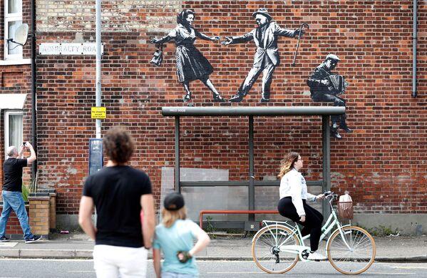 Unas personas observan una obra de arte callejero que se cree que es de autoría de Banksy en Great Yarmouth (Reino Unido) el 8 de agosto. - Sputnik Mundo