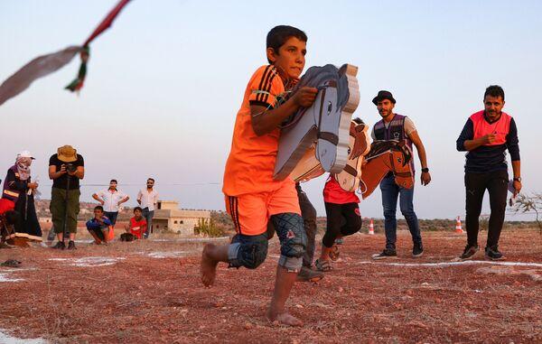 """Unos niños sirios desplazados participan de los llamados """"Juegos Olímpicos del Campamento 2020"""" en la ciudad de Fuaa (Siria), el último gran bastión rebelde de Idlib, el 7 de agosto. Esta edición de los JJOO para niños refugiados reunió cerca de 120 jóvenes de 12 campamentos diferentes. - Sputnik Mundo"""
