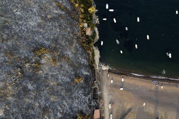 Una montaña quemada por los incendios forestales cerca de una playa en la isla de Eubea (Grecia) el 10 de agosto. - Sputnik Mundo