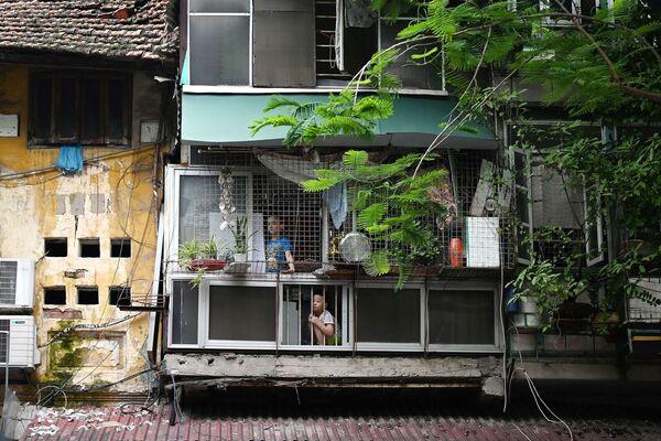 Unos niños miran las calles vacías desde el interior de su casa en Hanoi (Vietnam) el 11 de agosto, en medio de un nuevo lockdown de dos semanas impuesto por el Gobierno para detener la propagación del COVID-19 en el país. - Sputnik Mundo