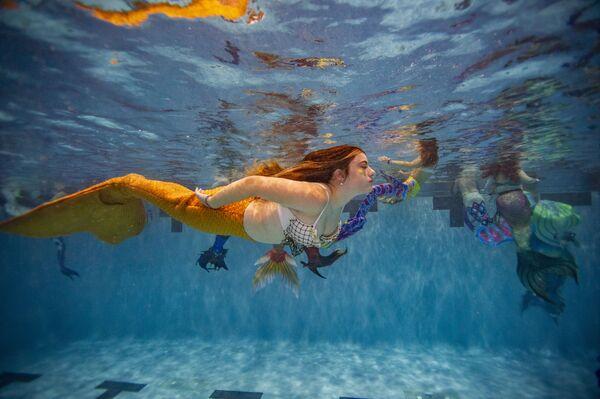 Unas personas participan en un evento acuático durante el MerMagic Con en Manassas, Virginia (EEUU) el 7 de agosto. Esta convención se autotitula la reunión de sirenas más grande del mundo. - Sputnik Mundo