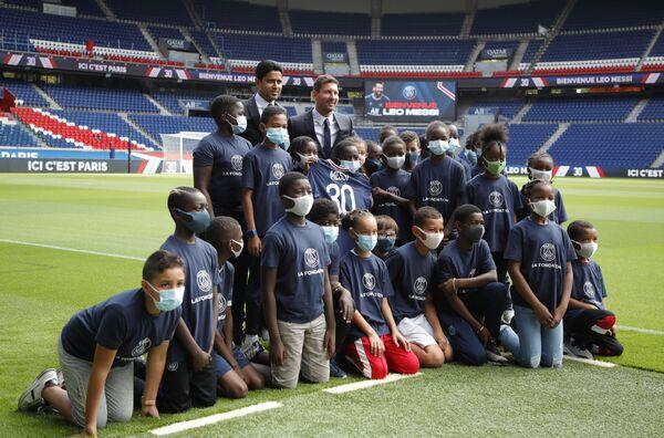 Su salario superará los 46 millones de dólares por temporada. En la foto: El director general del PSG, Nasser Al-Khelaifi, y Lionel Messi posan con varios niños en el estadio del club deportivo. - Sputnik Mundo