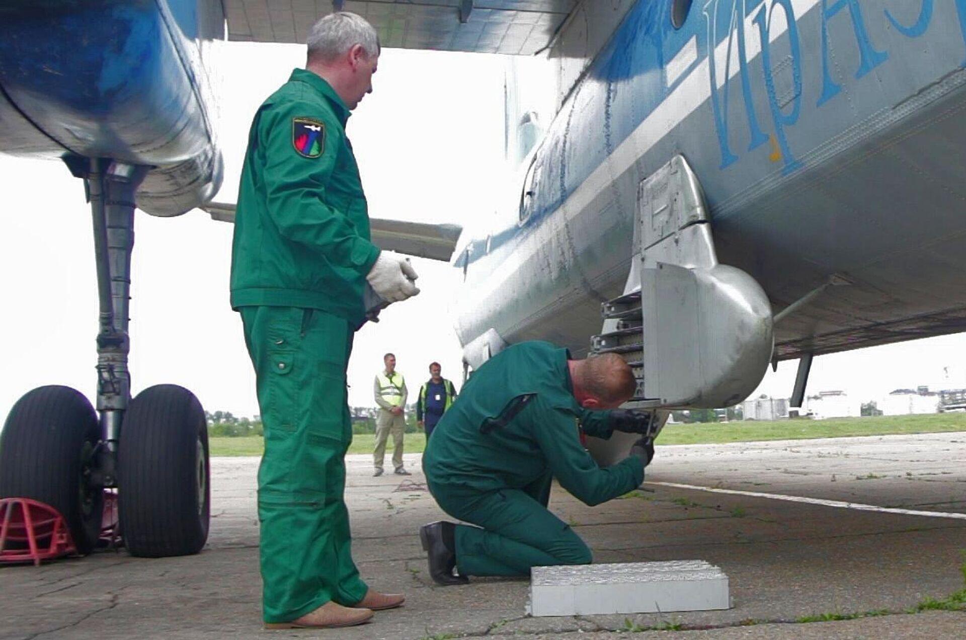 Unos trabajadores instalan cartuchos de yoduro de plata en el avión An-26 Tsiklon - Sputnik Mundo, 1920, 15.08.2021