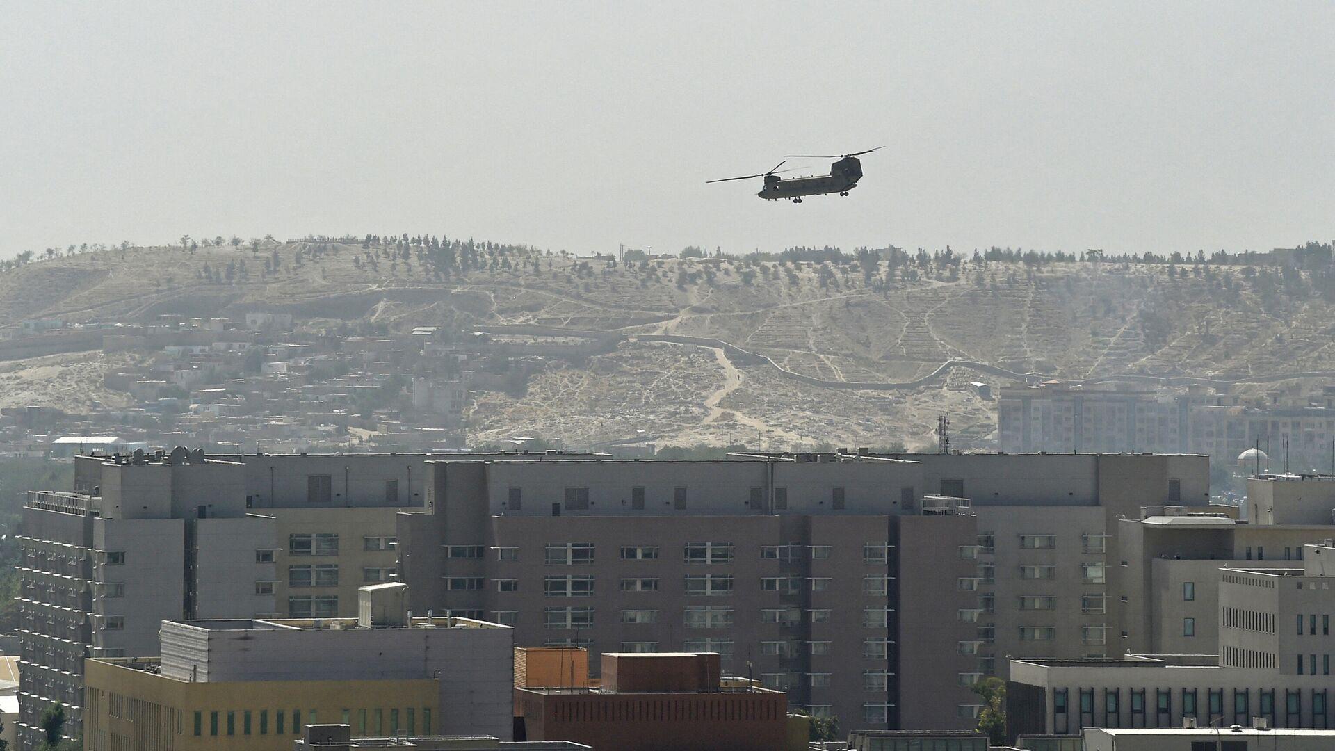 Un helicóptero militar estadounidense volando sobre la embajada de Estados Unidos en Kabul el 15 de agosto de 2021 - Sputnik Mundo, 1920, 16.08.2021