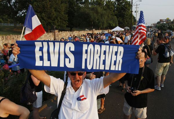 """Elvis Aaron Presley nació en la ciudad estadounidense de Tupelo, en Misisipi, pero a los 13 años la familia de la futura estrella del rocanrol decidió mudarse a Memphis, en el estado de Tennessee.En la foto: un fanático de Elvis Presley sostiene un cartel en el que se lee """"Elvis para siempre"""", mientras espera en una fila para visitar la tumba del artista en la víspera del 30 aniversario de su muerte, el 15 de agosto de 2007 en Tennessee (Estados Unidos). - Sputnik Mundo"""