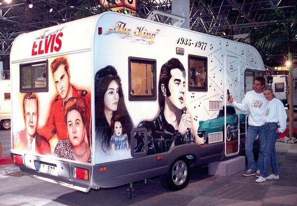 La noticia del fallecimiento de Presley se difundió rápidamente por las agencias de noticias de todo el mundo, causando una ola de conmoción a lo largo y ancho del planeta.En la foto: una pareja posa al lado de su autocaravana pintada con motivos de la vida de Elvis Presley en el Caravan Salon 97 en Düsseldorf (Alemania) el 26 de septiembre de 1997. - Sputnik Mundo