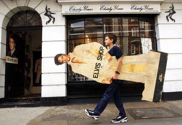 La versión oficial de la causa del fallecimiento del artista ha cambiado con el paso del tiempo, a medida que se realizaron nuevas investigaciones.En la foto: un niño carga una imagen de Elvis Presley a una tienda dedicada al cantante llamada Elvisly Yours en el centro de Londres (Reino Unido) el 16 de agosto de 2002. - Sputnik Mundo