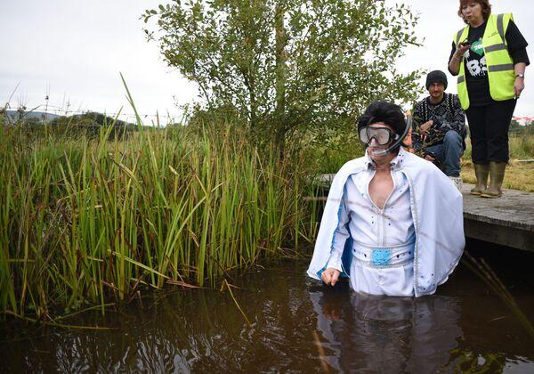 """Uno de los proyectos más destacados de la última década acerca del 'rey del rocanrol' fue su """"resurrección"""" a través de un holograma.En la foto: un hombre disfrazado de Elvis Presley se prepara para participar en el 30 Campeonato Mundial de Buceo en Pantanos en Llanwrtyd Wells (Reino Unido) el 30 de agosto de 2015. - Sputnik Mundo"""