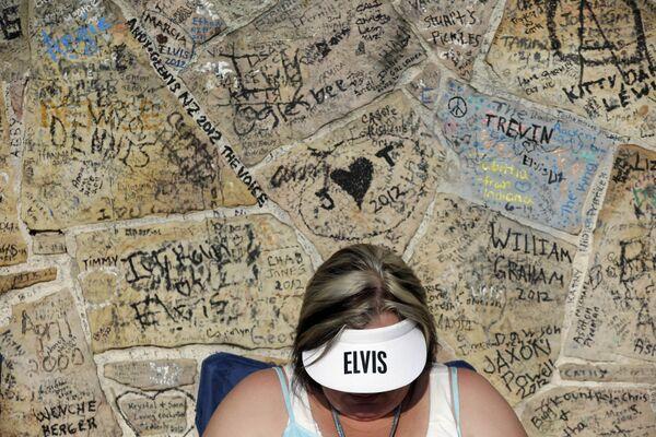 Actualmente, se llevan a cabo negociaciones con la exesposa del músico, Priscilla Presley, para la creación de un espectáculo completo de hologramas de Elvis en Las Vegas (EEUU).En la foto: una fan de Elvis Presley espera en una fila frente a Graceland, la casa del cantante en Memphis, el 15 de agosto de 2012 para participar en la vigilia anual a la luz de las velas con motivo del 35 aniversario de la muerte del artista. - Sputnik Mundo