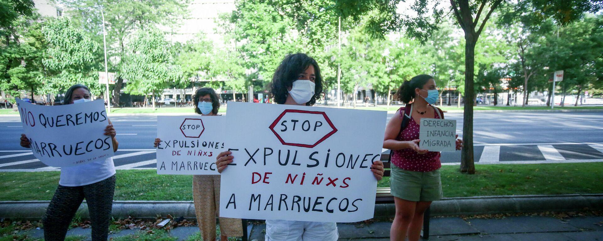 Participante lleva un cartel que dice 'Stop expulsiones de niñxs a Marruecos' durante una manifestación contra la deportación de los menores migrantes marroquíes - Sputnik Mundo, 1920, 16.08.2021