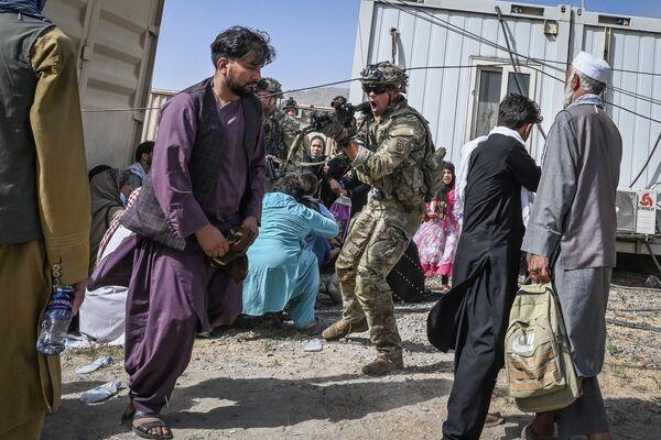 Un soldado estadounidense apunta a un afgano en el aeropuerto de Kabul, el 16 de agosto de 2021. El presidente afgano, Ashraf Ghani, dimitió y huyó del país el 15 de agosto. - Sputnik Mundo