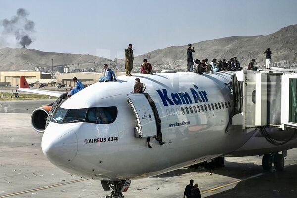 Multitud de afganos se encaraman a un avión con la esperanza de poder salir del país. Debido a la aglomeración en las pistas del aeropuerto, dos aviones militares enviados por Chequia y uno de Alemania no pudieron aterrizar en el aeropuerto. - Sputnik Mundo