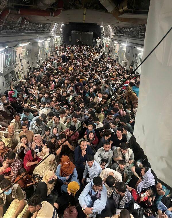 La gente evacuada agolpada en el interior de un avión de transporte C-17 Globemaster III de la Fuerza Aérea de Estados Unidos. El vuelo militar estadounidense logró evacuar a 640 afganos a Catar desde Kabul. La foto fue tomada el 15 de agosto de 2021. - Sputnik Mundo