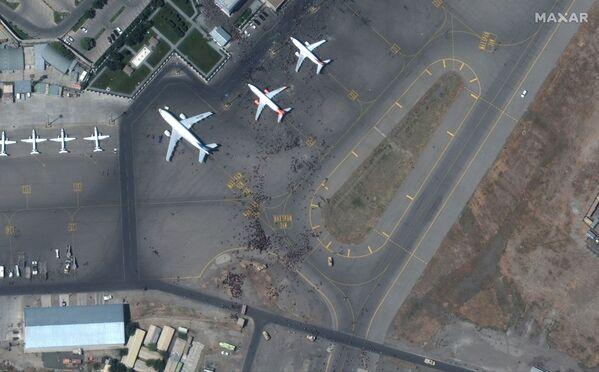 La pista del aeropuerto de Kabul llena de personas el 16 de agosto de 2021. Los militares estadounidenses tuvieron que abrir fuego de advertencia para dispersar a la muchedumbre de la pista de aterrizaje. Ya son más de 10 las víctimas mortales del caos que se desató en el aeropuerto. - Sputnik Mundo