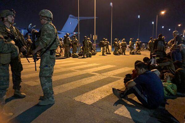 Soldados franceses hacen guardia mientras ciudadanos de Francia y sus colegas afganos esperan para subir a un avión de transporte militar en el aeropuerto de Kabul, el 17 de agosto de 2021. - Sputnik Mundo