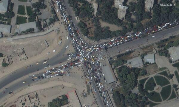 Atascos de coches y multitud de personas alrededor del aeropuerto de Kabul para intentar huir del país ante el avance del régimen talibán, el 16 de agosto de 2021. Las personas abandonan sus vehículos y acuden al aeródromo a pie. - Sputnik Mundo