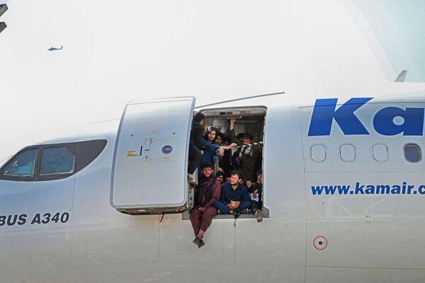 Varios afganos se encaraman a un avión con la esperanza de poder salir de su país. - Sputnik Mundo