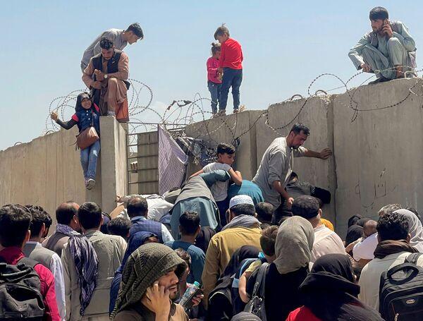 Un hombre agarra a una chica para entrar en el aeropuerto internacional Hamid Karzai en Kabul, Afganistán, el 16 de agosto de 2021. Es el único punto desde donde miles de afganos pueden abandonar su país. Los militares estadounidenses lo custodian. - Sputnik Mundo