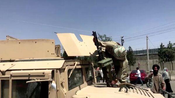 Un terrorista talibán en un vehículo blindado carga su arma en el exterior del aeropuerto en Kabul, en Afganistán. - Sputnik Mundo