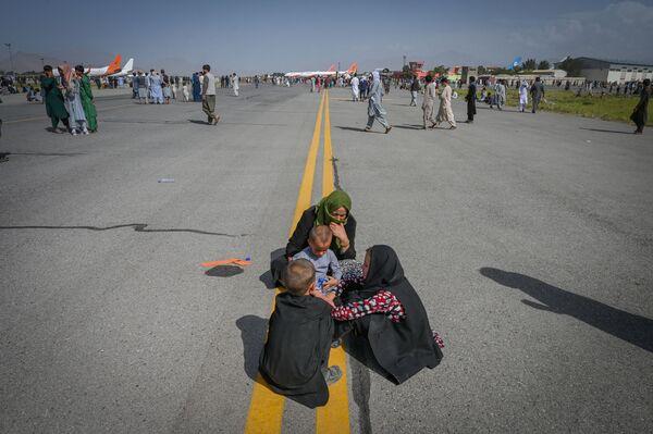 La pista de aterrizaje del aeropuerto internacional de Kabul. La gente espera para abandonar el país después de 20 años de guerra en Afganistán. - Sputnik Mundo