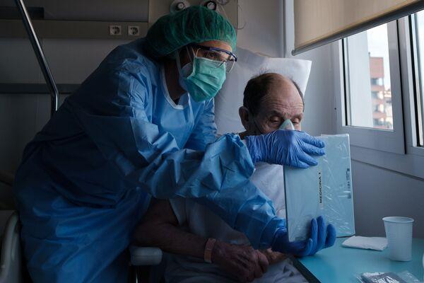 Los pacientes de los hospitales de COVID-19 solo pueden ver a sus seres queridos en las pantallas de sus smartphones. En esta foto de Carles Ramos, titulada Video calls (Videollamadas), una enfermera le muestra una tableta a un paciente. La conmovedora instantánea ganó en la categoría Tecnologías. - Sputnik Mundo