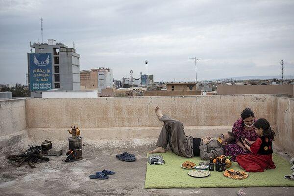 La obra de Younes Mohammad Nawroz (Nouruz) ocupó el segundo peldaño en la categoría Cuarentena. Muestra a una familia iraquí celebrando la festividad religiosa —normalmente multitudinaria— en la azotea de su casa debido a la pandemia. - Sputnik Mundo