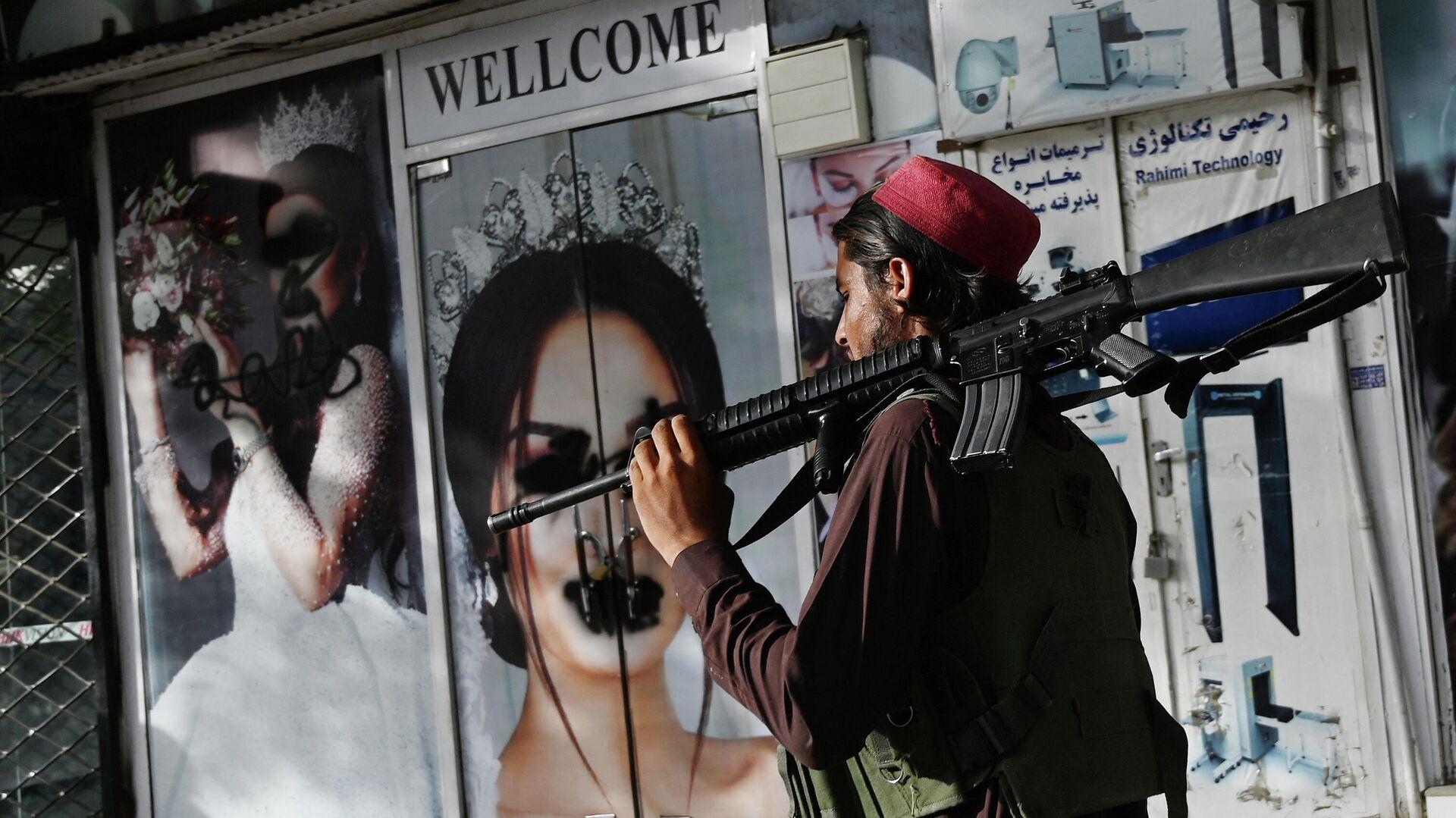 Un soldado talibán camina frente a un salón de belleza con imágenes de mujeres desfiguradas con spray, en Shar-e-Naw en Kabul, el 18 de agosto de 2021 - Sputnik Mundo, 1920, 23.08.2021