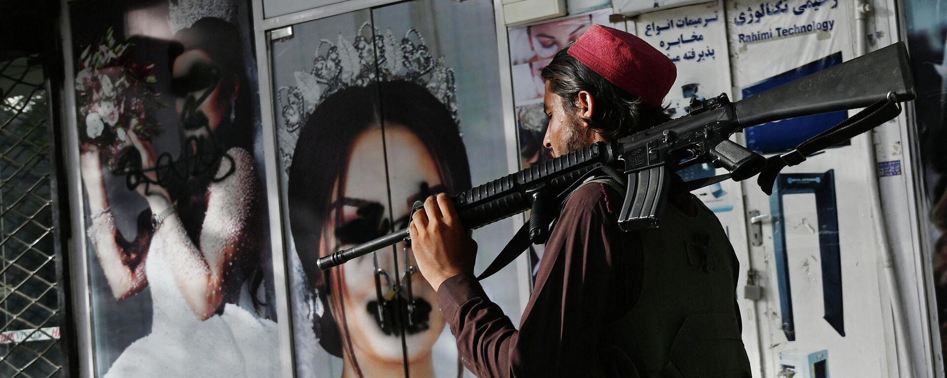 Un soldado talibán camina frente a un salón de belleza con imágenes de mujeres desfiguradas con spray, en Shar-e-Naw en Kabul, el 18 de agosto de 2021 - Sputnik Mundo, 1920, 18.08.2021