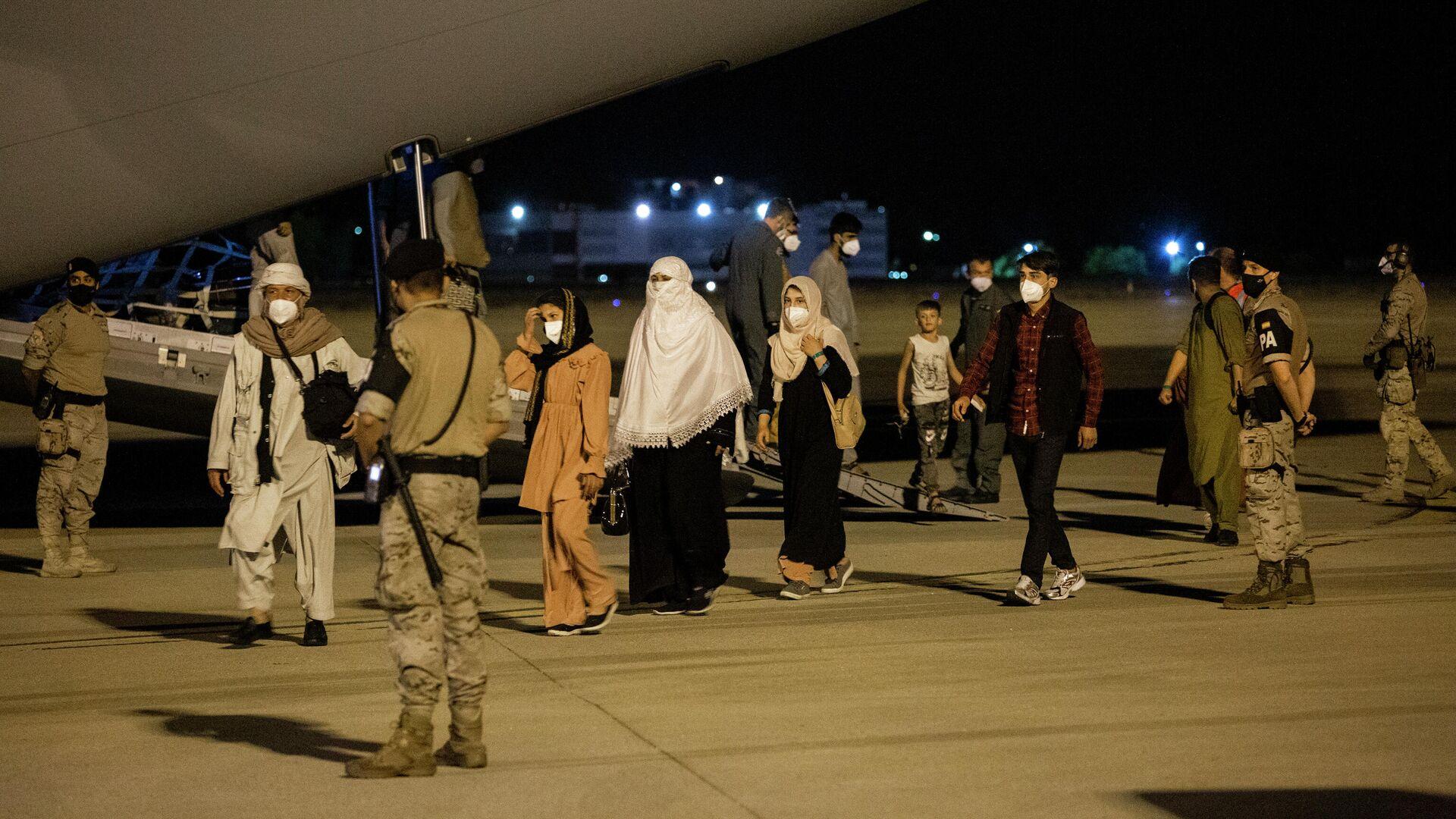 Varias personas repatriadas llegan a la pista tras bajarse del avión A400M en el que ha sido evacuados de Kabul, a 19 de agosto de 2021, en Torrejón de Ardoz, Madrid - Sputnik Mundo, 1920, 23.08.2021