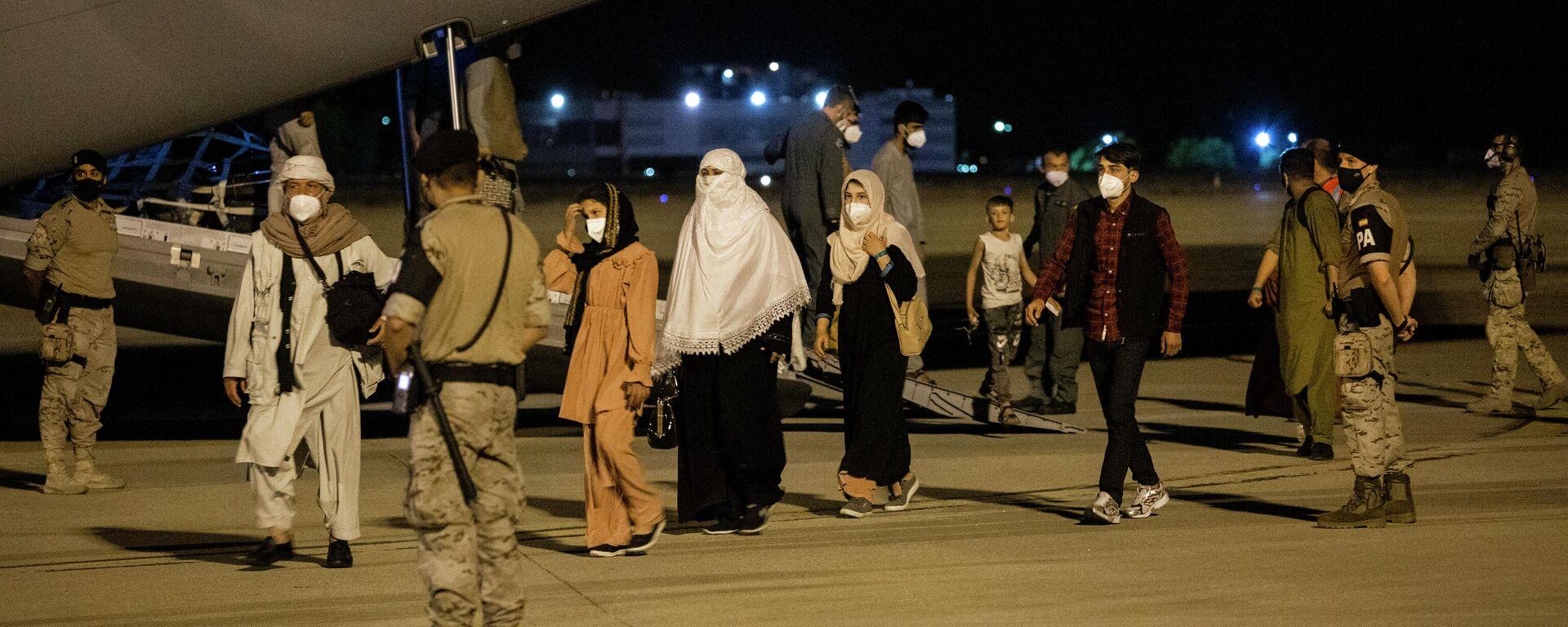 Varias personas repatriadas llegan a la pista tras bajarse del avión A400M en el que ha sido evacuados de Kabul, a 19 de agosto de 2021, en Torrejón de Ardoz, Madrid - Sputnik Mundo, 1920, 19.08.2021