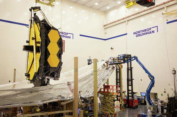 En esta imagen de enero de 2021, técnicos e ingenieros trabajan en el parasol del telescopio espacial. Diseñado para proteger la óptica del telescopio de cualquier fuente de calor que pudiera interferir con su visión, el parasol es uno de los componentes más críticos y complejos de Webb. Dado que el Webb es un telescopio de infrarrojos, sus espejos y sensores deben mantenerse a temperaturas extremadamente frías para detectar las débiles señales de calor procedentes de objetos lejanos en el universo. - Sputnik Mundo