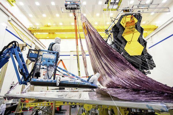 Tomada en febrero de 2021, esta imagen muestra el parasol del telescopio espacial James Webb siendo plegado y embalado por ingenieros y técnicos de Northrop Grumman. El parasol tiene una estructura de cinco capas en forma de diamante del tamaño de una pista de tenis, y ha sido especialmente diseñado para plegarse alrededor de los dos lados del telescopio, y caber dentro de los límites del cohete Ariane 5. Completamente desplegado, mide 21 metros por 14 metros, pero dentro del cohete (de 17 metros de largo y 5,4 metros de diámetro) ocupará un área muy reducida. - Sputnik Mundo