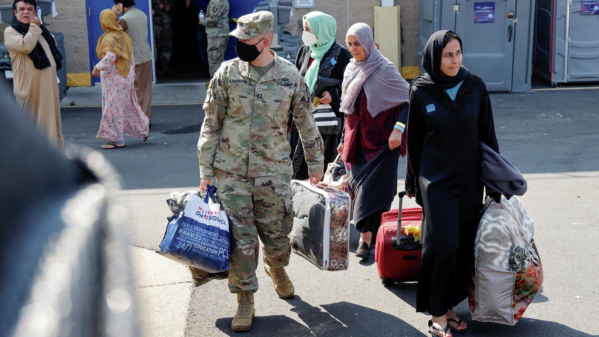 Los militares estadounidenses ayudan a las familias cuando salen de un centro para evacuados de Afganistán en el Dulles Expo Center cerca del Aeropuerto Internacional de Dulles en Chantilly, Virginia, EEUU, 25 de agosto de 2021 - Sputnik Mundo, 1920, 26.08.2021