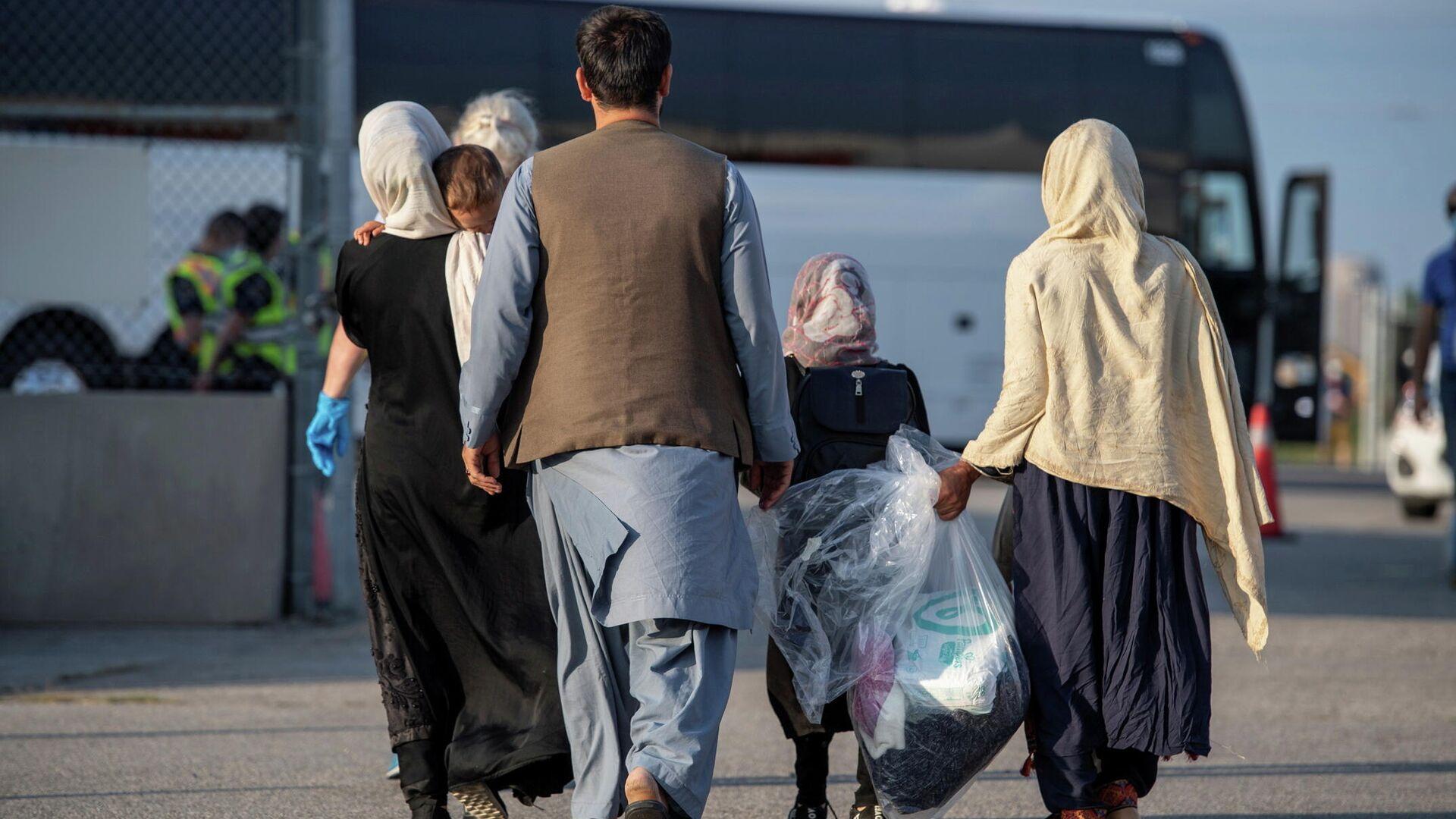 Los refugiados afganos que apoyaron la misión de Canadá en Afganistán se preparan para abordar los autobuses después de llegar a Canadá, en el Aeropuerto Internacional Toronto Pearson el 24 de agosto de 2021 - Sputnik Mundo, 1920, 26.08.2021