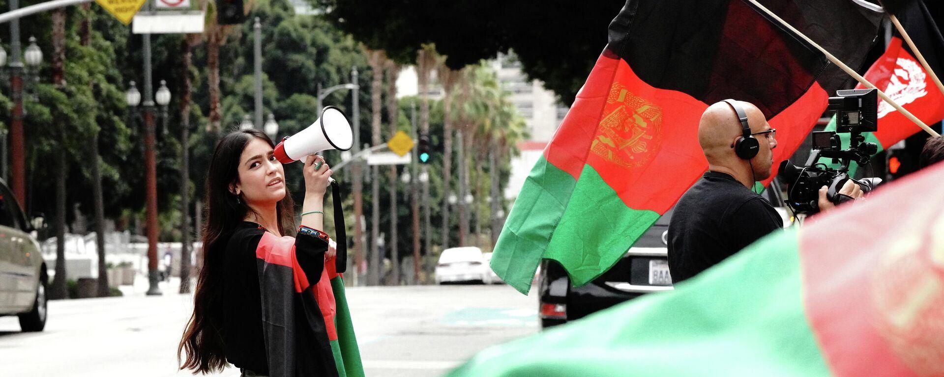 La inmigrante afgano-estadounidense Hameeda Uloomi, de 18 años, con un megáfono, en un mitin que organizó contra los talibanes y los acontecimientos en Afganistán, durante una manifestación en el centro de Los Ángeles, California, Estados Unidos, el 21 de agosto de 2021 - Sputnik Mundo, 1920, 27.08.2021