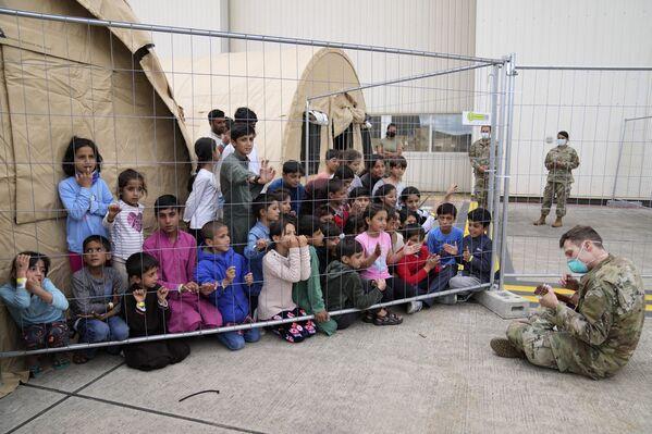Un soldado estadounidense toca la guitarra ante un grupo de menores afganos refugiados en la base estadounidense de Rammstein (Alemania). - Sputnik Mundo