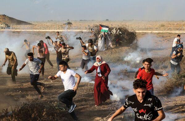 Manifestantes palestinos y periodistas huyen de los soldados israelíes en Gaza. - Sputnik Mundo