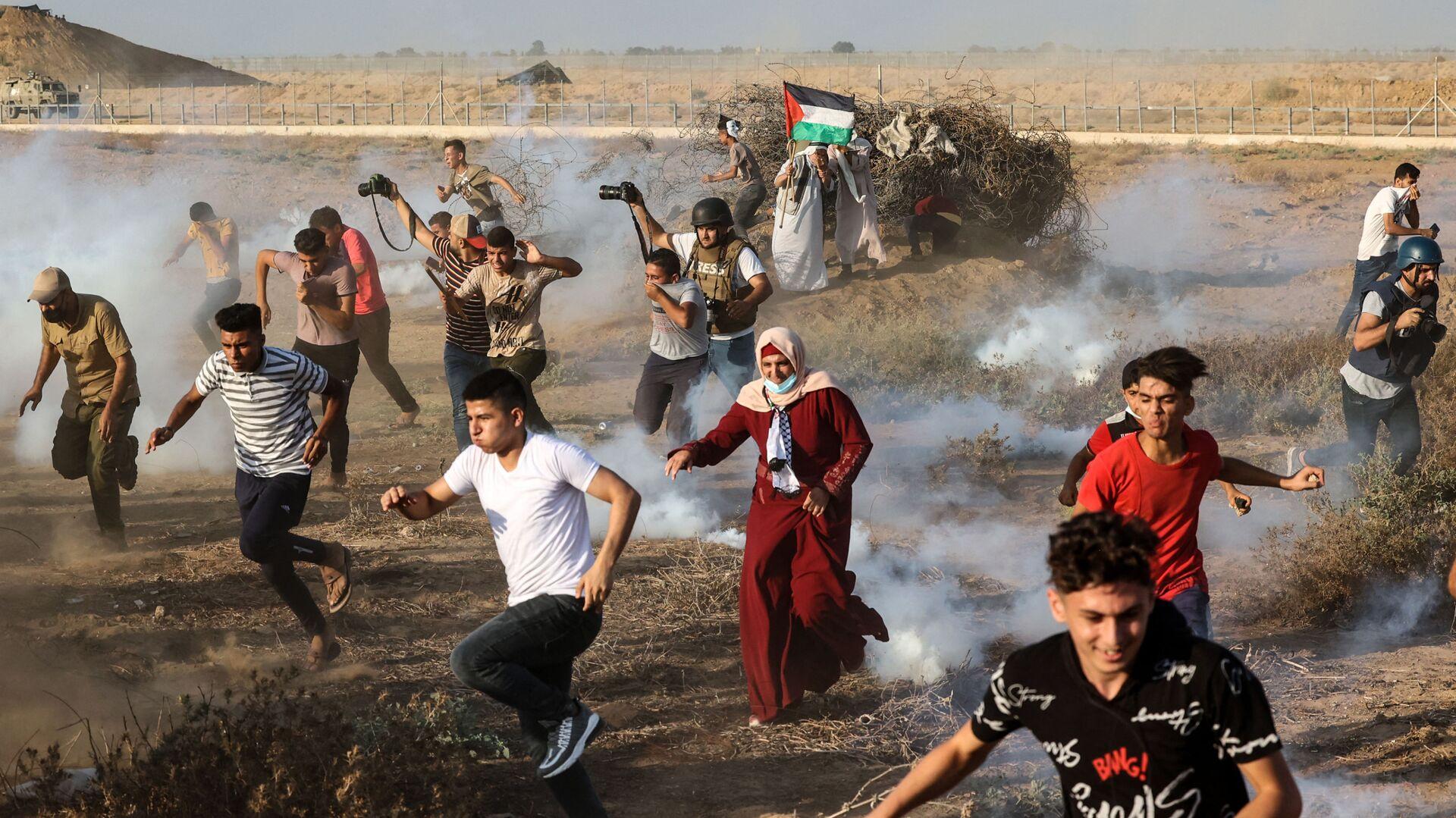Палестинские демонстранты и журналисты бегут от слезоточивого газа во время акции протеста на юге сектора Газа - Sputnik Mundo, 1920, 13.09.2021