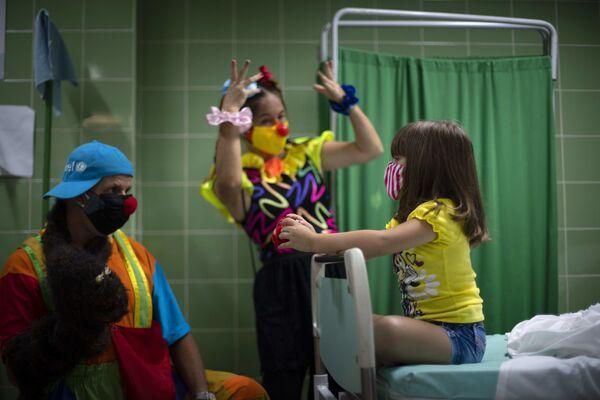 Payasos entretienen a una pequeña paciente durante la campaña de vacunación en La Habana (Cuba). - Sputnik Mundo