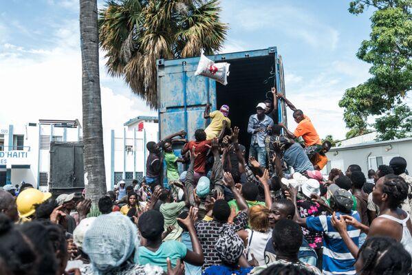 Trabajadores humanitarios reparten alimentos a los vecinos de la localidad de Les Cayes (Haití). - Sputnik Mundo