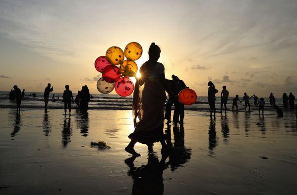Una mujer vende globos en una playa de Bombay (India). - Sputnik Mundo
