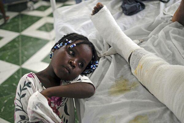 Una niña descansa al lado de su madre herida en el terremoto de Haití. - Sputnik Mundo