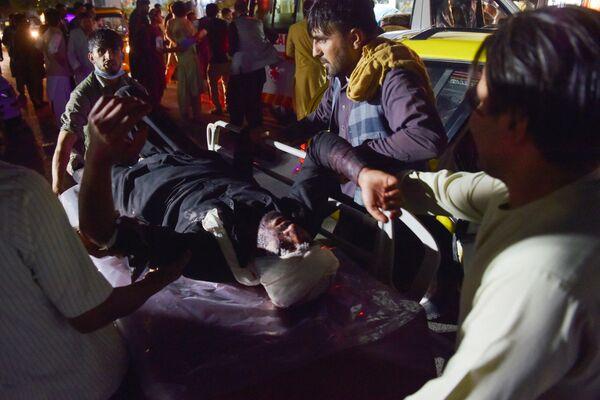 La primera explosión ocurrió alrededor de las 6 pm, hora local, en la entrada norte del aeropuerto de Kabul. Fue causado por un atacante suicida que activó un artefacto explosivo en medio de una multitud de afganos que se encontraban en el lugar con la esperanza de volar fuera de Afganistán. En la foto: los médicos ayudan a las víctimas de las explosiones en Kabul. - Sputnik Mundo