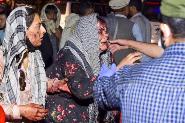 Mujeres ensangrentadas tras el mortífero ataque terrorista frente al aeropuerto de Kabul (Afganistán). - Sputnik Mundo